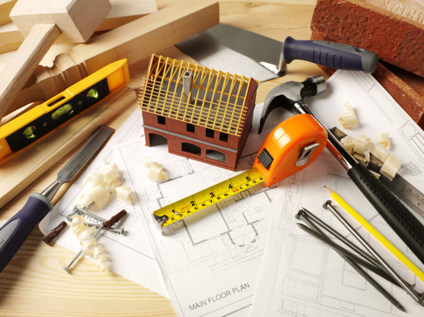 Work Tools with a Toy Model House on Paper Plans